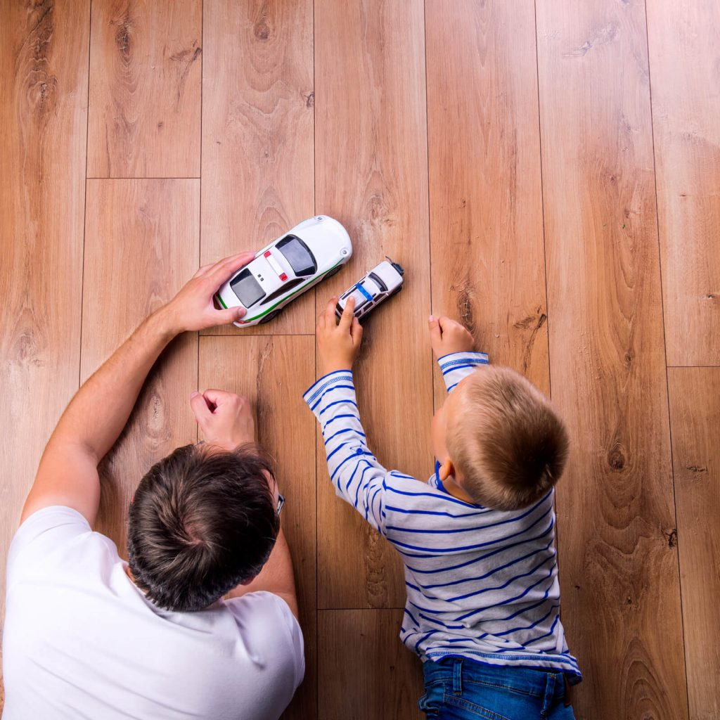 Father with kid playing with toycar | Reinhold Flooring